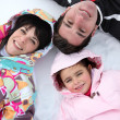 Family lying in the snow — Stock Photo