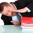 Royalty-Free Stock Photo: Businessman examining his pile of work