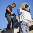 Foto Stock: Two roofers hard at work