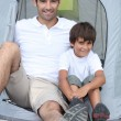 Father and son in front of tent - Stock Photo
