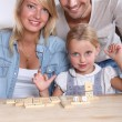 Parents and daughter playing dominoes — Stock Photo