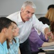 Teacher pointing to computer screen - Stock Photo