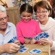 Little girl playing cards with her grandparents — Stock Photo
