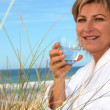 Woman with a bathrobe and a glass of water at the beach - Stock Photo