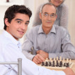 Grandfather and grandson playing chess — Stock Photo #9324325