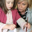 Mother and daughter painting figurine — Stock Photo