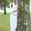 Woman standing next to a tree — Stock Photo #9325284