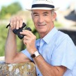 Senior mwith pair of binoculars — Stock Photo #9325578
