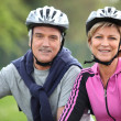 Senior couple on a bicycle with helmet — Stock Photo #9325777