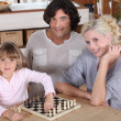 Little girl playing chess with her parents — Stok fotoğraf