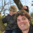 Little boy climbing tree with father — Stock Photo