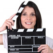 Stock Photo: Womusing movie clap