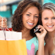 Stock Photo: Friends out shopping with a cellphone