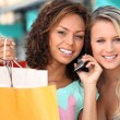 Friends out shopping with a cellphone — Stock Photo