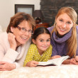 Grandmother, mother, and daughter lying on a bed — Stock Photo #9326697