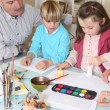 Stock Photo: Man watching grandchildren paint