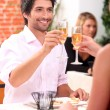 Couple celebrating in restaurant - Stock Photo