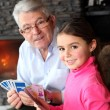 Old man playing card game with his granddaughter — Stock Photo