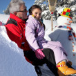 Stock Photo: Little girl making a snowman with grandpa