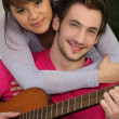Girl hugging boy with guitar - Stockfoto