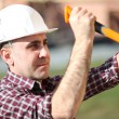 Builder taking out nails with a hammer — Stock Photo