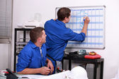 Manual workers writing on a calendar — Stock Photo