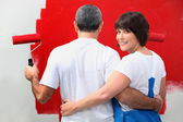 Couple painting wall in red — Stock Photo