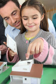 Little girl playing with scale model of housing — Stock Photo