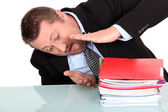 Businessman examining his pile of work — Stock Photo