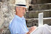 Elderly man sat on steps with laptop — Stock Photo