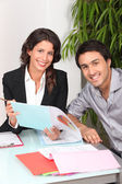 Two cheerful workers looking at financial information — Stock Photo