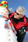 Homem sênior com um boneco de neve — Foto Stock