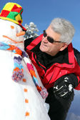 Starší muž s sněhulák — Stock fotografie