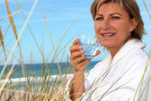 Woman with a bathrobe and a glass of water at the beach — Stock Photo