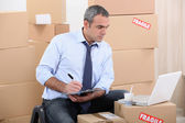 Man surrounded by cardboard boxes using a laptop — Stockfoto