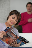 Woman reading magazine on sofa — Stock Photo