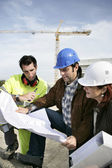 Construction team looking at plans — Stock Photo