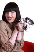 Woman with several pairs of sunglasses — Stock Photo