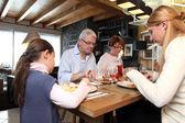 Family gathered around table — Stock Photo
