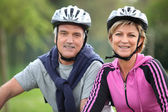Senior couple on a bicycle with helmet — Stock Photo