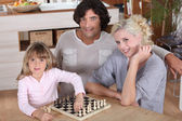 Little girl playing chess with her parents — Stock Photo