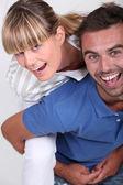 Man giving girlfriend piggyback — Stock Photo