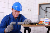 Craftsman assembling pipes — Stock Photo