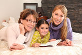 Grandmother, mother, and daughter lying on a bed — Stockfoto