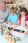 Man watching grandchildren paint — Stock Photo