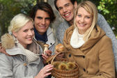 Group of young with a basket of chestnuts and mushrooms — Stock Photo