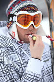 Skier applying lip balm — Stock Photo