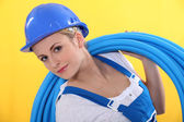 Blond plumber carrying plastic piping — Stock Photo