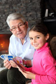 Old man playing card game with his granddaughter — Foto Stock