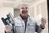 Handyman covered in dust after sanding room — Stock Photo